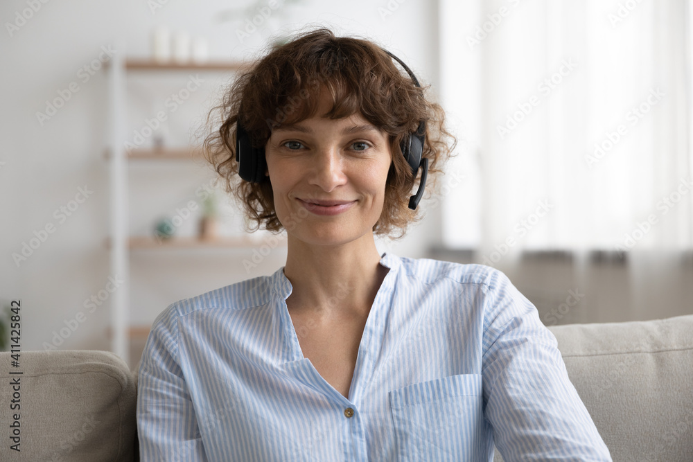 Fototapeta Portrait of smiling young Caucasian woman in headphones sit on sofa at home talk on video call. Happy female in earphones have webcam digital conference or online virtual communication with client.