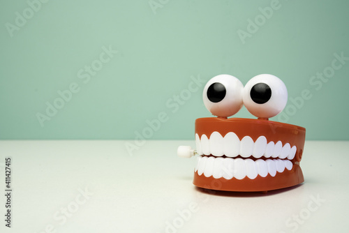 Fotografie, Obraz Dentures And Goggly Eyes On Table Against Wall