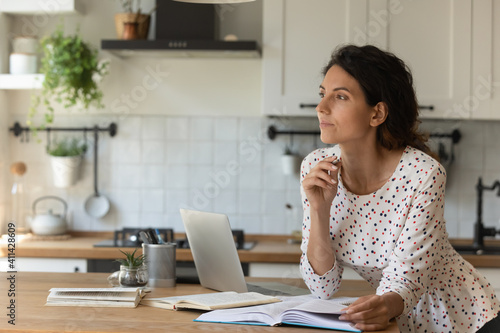 Obraz Pensive millennial Caucasian woman distracted from online work look in distance dreaming or thinking. Thoughtful young female study distant on laptop make decision or plan. Education concept. - fototapety do salonu