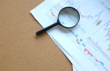 High Angle View Of Magnifying Glass On Graph Charts