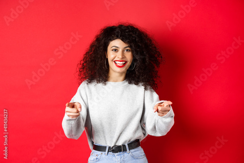 Fotografija Cheerful woman with curly hair inviting you, recruiting newbies, pointing finger
