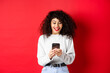 Leinwandbild Motiv Image of young woman with curly hair, reading message on smartphone and smiling happy, receiving good news online, standing on red background
