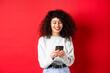 Leinwandbild Motiv Happy positive girl chatting on phone, reading message and smiling, using social media app, standing on red background