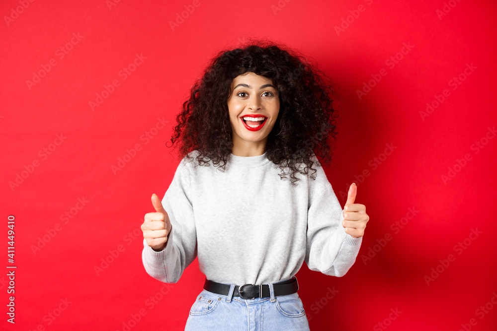 Fototapeta Enthusiastic girl with curly hair and red lips, showing thumbs up and saying yes, agree with you, compliment good work, like something cool, standing on studio background