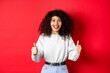 Leinwandbild Motiv Enthusiastic girl with curly hair and red lips, showing thumbs up and saying yes, agree with you, compliment good work, like something cool, standing on studio background