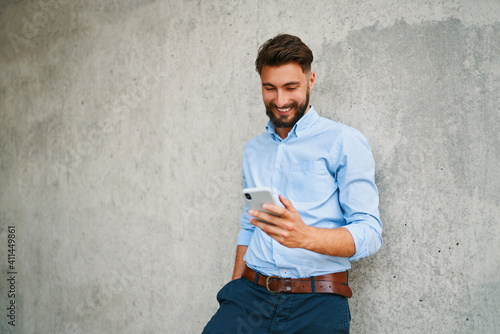 Fototapeta Handsome young businessman using smartphone while out in the city on break obraz