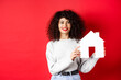 Leinwandbild Motiv Real estate. Smiling caucasian woman with curly hair and red lips, showing paper house model, searching property, standing on red background