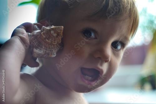 Fototapeta Close-up Portrait Of Cute Boy Holding Conch Shell