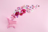Fototapeta Kawa jest smaczna - Flowers fly out of the pink shopping cart on a pink background. Season sale, spring shoping concept. Valentines day.