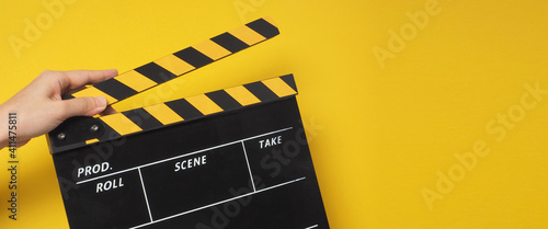 Tela hand is holding yellow clapper board or movie slate or clapperboard