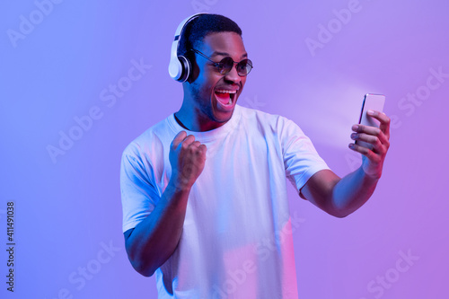 Online Gaming. Excited Black Guy In Headphones Celebrating Success With Smartphone