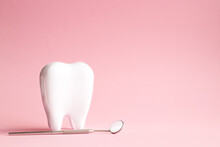 White Tooth With Dental Mirror On Pink Background In Honor Of International Dentist Day With Place For Text