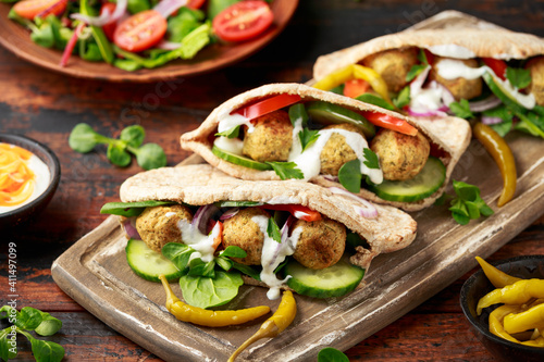 Photo Vegetarian Chickpea falafel pita bread with pickled chilies and fresh salad