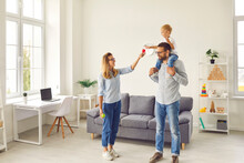 Happy Family With Little Smiling Boy Son On Fathers Shoulders Staying At Home And Playing Together With Room Interior Around. Happy Family And Childhood, Spending Time Together Concept