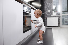 Infant Baby Boy Near Oven In Home Kitchen.