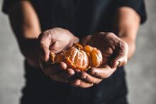 Ripe Juicy Sweet Orange Mandarins In A Human Hand Against A Dark Background.