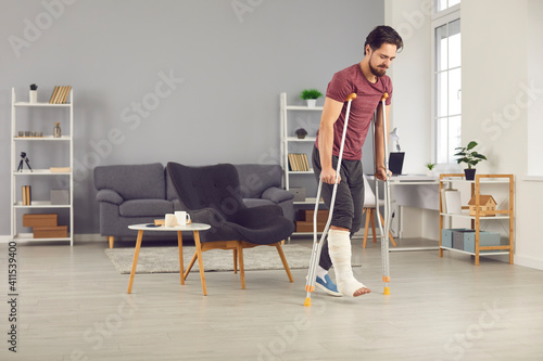 Fototapeta Successful rehabilitation and recovery of people after physical injury such as bone fracture in car or home accident: Young man with broken leg trying to walk with crutches and making good progress obraz