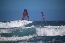 Ocean Waves With Red Sails Of Windsurfers In Background In Bokeh (Tenerife, Spain)