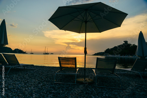 Fototapeta view of sea beach with sun loungers and umbrellas