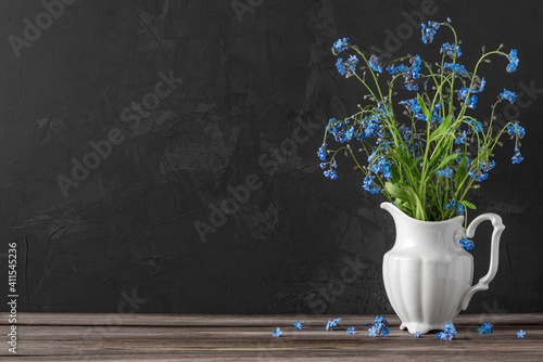 Fototapeta Still life with forget me not flowers bouquet in vase on dark background with copy space. festive background obraz