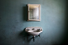 Sink And Mirror Inside An Abandoned Asylum.