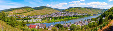 Enkirch, Rhineland-Palatinate, Germany. Panoramic View Of The River Moselle With The Village Enkirch And The Surrounding Vineyards Of The Moselle Valley On A Sunny Afternoon.