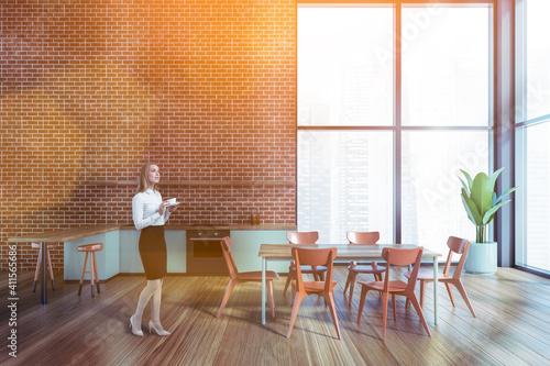 Fotografia Attractive business woman drinking coffee at corporate kitchen in skyscraper office