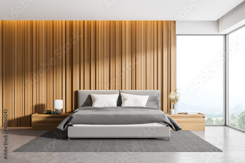 Fototapeta Corner of master bedroom with wooden walls, panoramic window with countryside view, comfortable king size bed standing on gray carpet and concrete floor. obraz