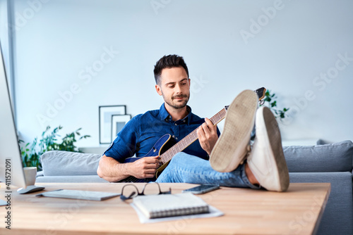 Fototapeta Man playing on the guitar while working from home office