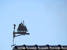 An Ancient Weather Vane In The Shape Of A Fishing Schooner Over The Roof Of A House Against The Blue Sky In The Skåne Region, Sweden.