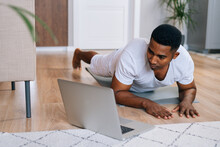 Close-up View Of Strong African-American Man Exercising Workout In Horizontal Plank Position Using Laptop Computer To Watching Yoga And Training Video Digital Tutorial.