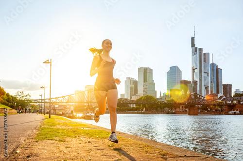 Obraz Junge Frau joggt am Mainufer, Frankfurt am Main, Hessen, Deutschland  - fototapety do salonu