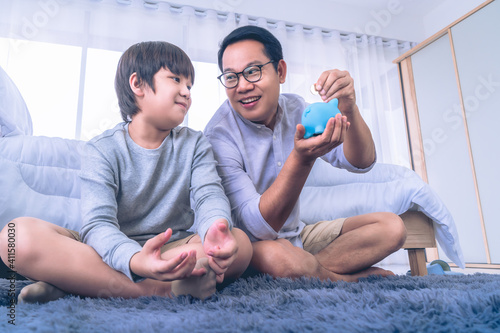 Asian Father is teaching his son in money saving by inserting coin into a blue piggy bank for Financial Education concept Wallpaper Mural