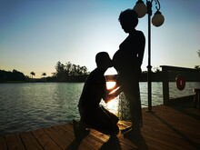 Side View Of Silhouette Man Kissing Pregnant Woman Belly On Pier Over Lake