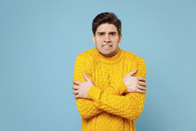 Young Caucasian Frozen Sick Ill Student Man 20s Wearing Casual Knitted Cozy Yellow Fashionable Sweater Looking Camera Hugging Himself With Crossed Hands Isolated On Blue Background Studio Portrait.