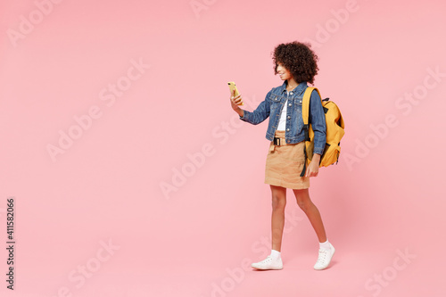 Obraz Full length happy smart smiling little african american kid school girl 12-13 year old in casual denim clothes backpack hold hands back of head isolated on pink background Childhood education concept - fototapety do salonu
