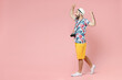 Full length side view of excited traveler tourist man in summer clothes hat doing winner gesture celebrating isolated on pink background. Passenger traveling on weekends. Air flight journey concept.