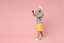 Full Length Side View Of Funny Traveler Tourist Man In Summer Clothes Hat Taking Pictures On Vintage Photo Camera Isolated On Pink Background. Passenger Travel On Weekends. Air Flight Journey Concept.