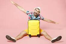 Full Length Of Excited Young Traveler Tourist Man In Hat Sit On Floor Near Suitcase Spreading Hands Like Flying Isolated On Pink Background. Passenger Traveling On Weekend. Air Flight Journey Concept.