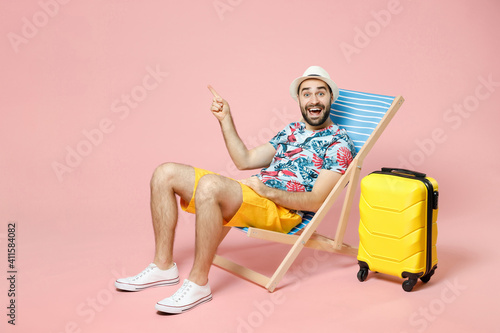 Fototapeta Full length of excited traveler tourist man in summer clothes hat sit on deck chair point index finger aside up isolated on pink background. Passenger traveling on weekend. Air flight journey concept. obraz na płótnie