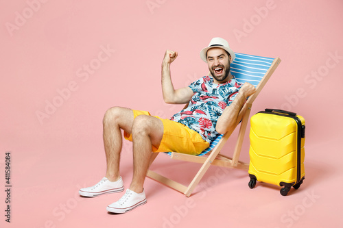 Fototapeta Full length happy young traveler tourist man in summer clothes hat sit on deck chair clenching fists like winner isolated on pink background. Passenger travel on weekend. Air flight journey concept. obraz na płótnie