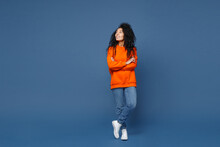 Full Length Of Attractive Smiling Young African American Woman In Casual Basic Bright Orange Sweatshirt Standing Holding Hands Crossed Looking Aside Isolated On Blue Color Background Studio Portrait.