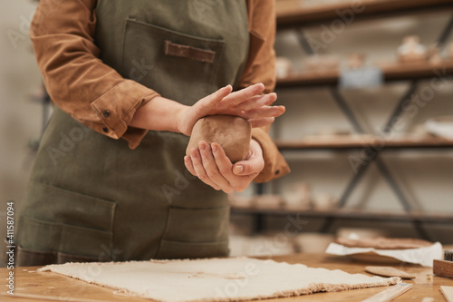 Fototapety, obrazy: Warm toned close up of young woman shaping clay while making ceramics in pottery workshop, small business concept, copy space