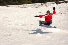 Boy Sledding Down Snowy Hill Getting Air From Jump