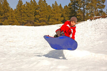 Young Boy Sledding Down Snowy Hill Getting Air From Jump