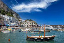 Marina With Yachts And Boats At Capri Island Town. View Of Boat Harbor And Marina Grande, On The Island Of Capri, With Colorful Buildings And High Mountains In The Background, Tyrrhenian Sea, Italy