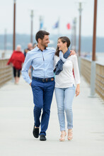 A Couple Walking On A Pier On A Lakeside