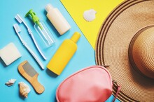 Luggage And Summer Travel Accessories Bag, Toiletries Kit. Flat Lay Composition Object Photography. Soap Bar, Toothbrushes, Empty Bottles For Cosmetics, Sunscreen Cream, Bag And Hat