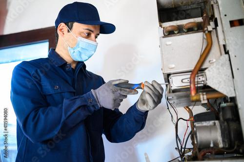 Fototapeta Smiling technician repairing an hot-water heater wearing a mask, coronavirus concept obraz