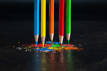 Five Sharpened Crayons In The Primary Colors Of The Spectrum Stand Upright Against A Dark Background In Multicolor Shavings Of Pencil Leads. Shallow Depth Of Field. Focused On Red